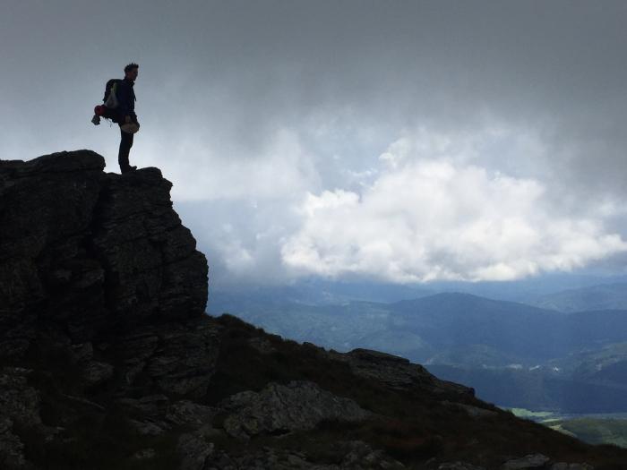 Človek stojaci na vrchu a obzerajúci sa okolo seba.